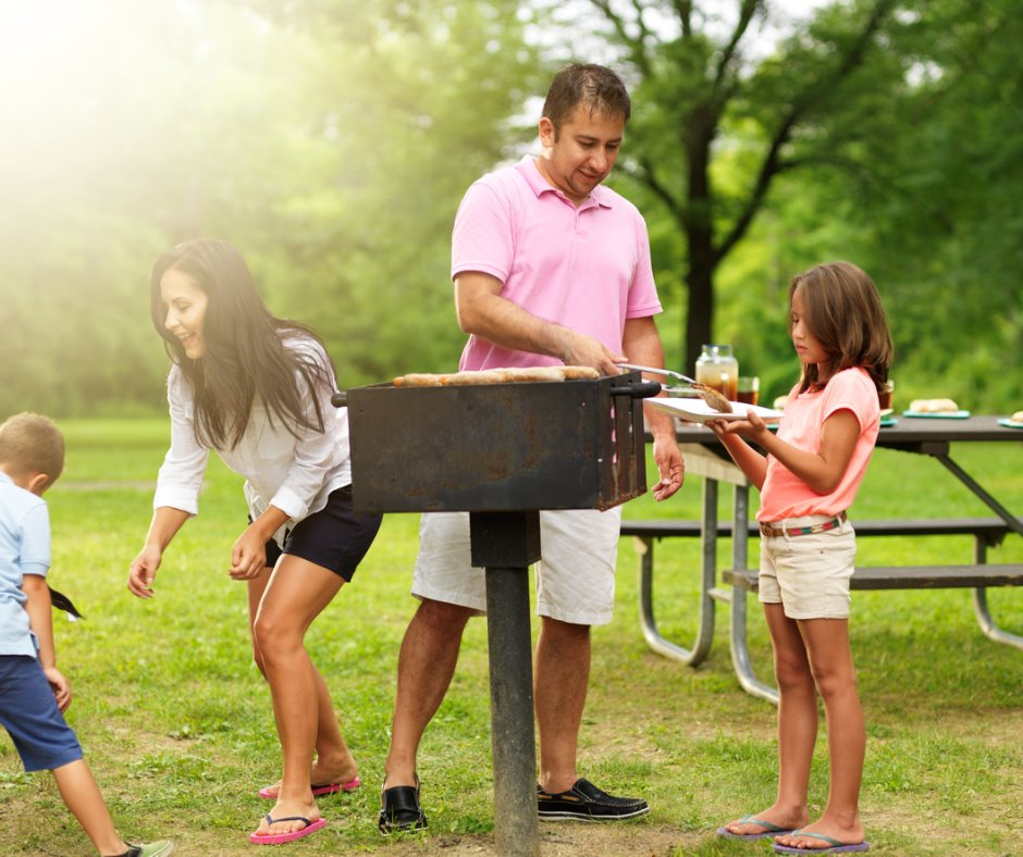 A family grills at a picnic area.