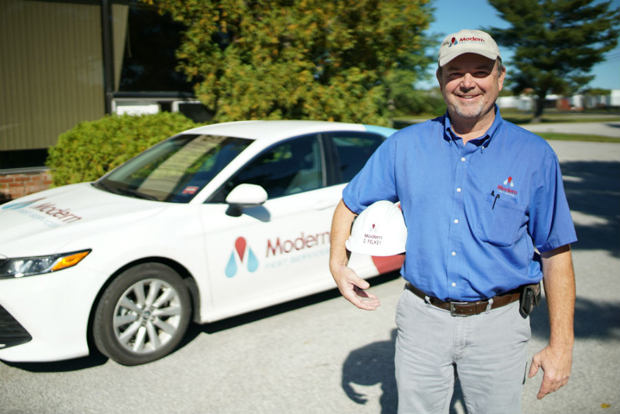Modern Pest specialist smiling and holding a hard hat while standing in front of a car with a Modern Pest logo