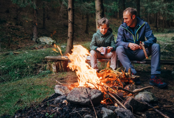 Father and son sit near a campfire in the woods in their permethrin-treated clothes.