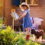 child girl watering flowers with her dog in summer garden, little helpers, outdoor activities
